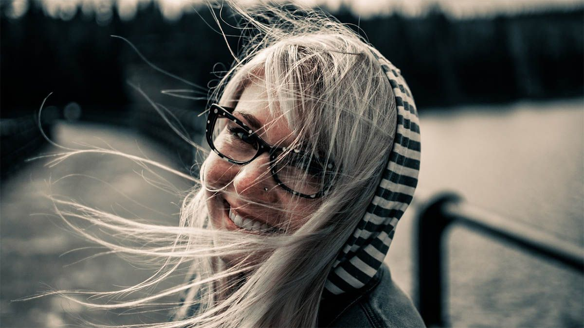 frau-blond-brille-haare-im-wind