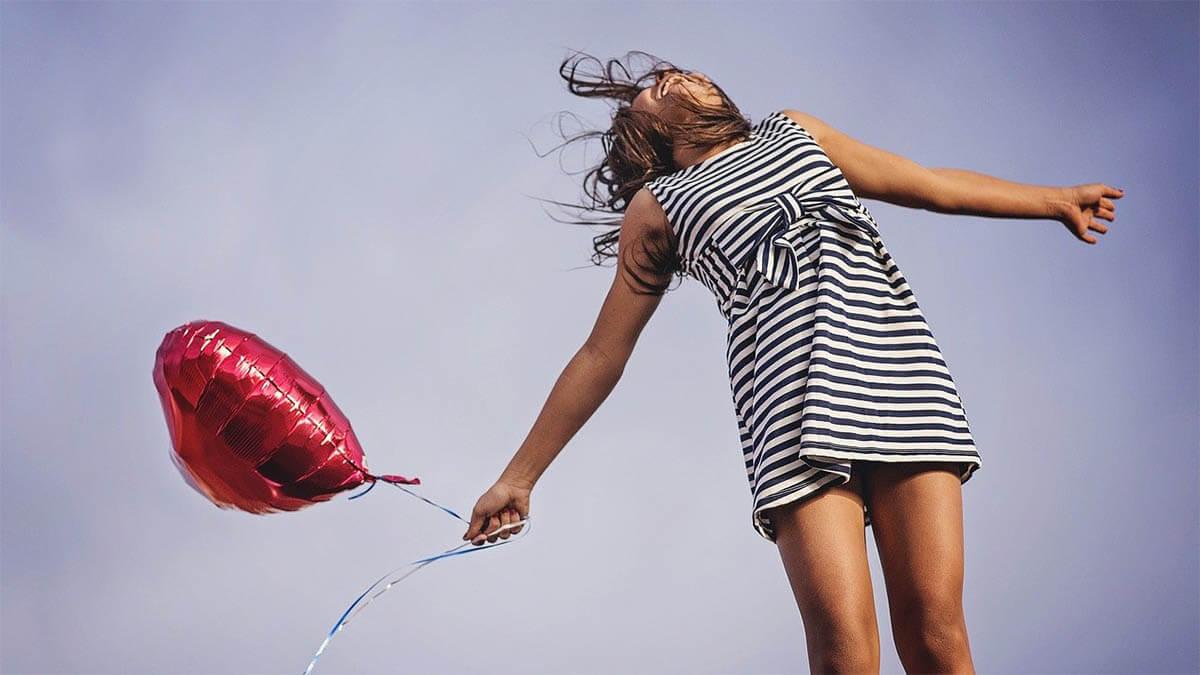 frau-gluecklich-mit-herzluftballon