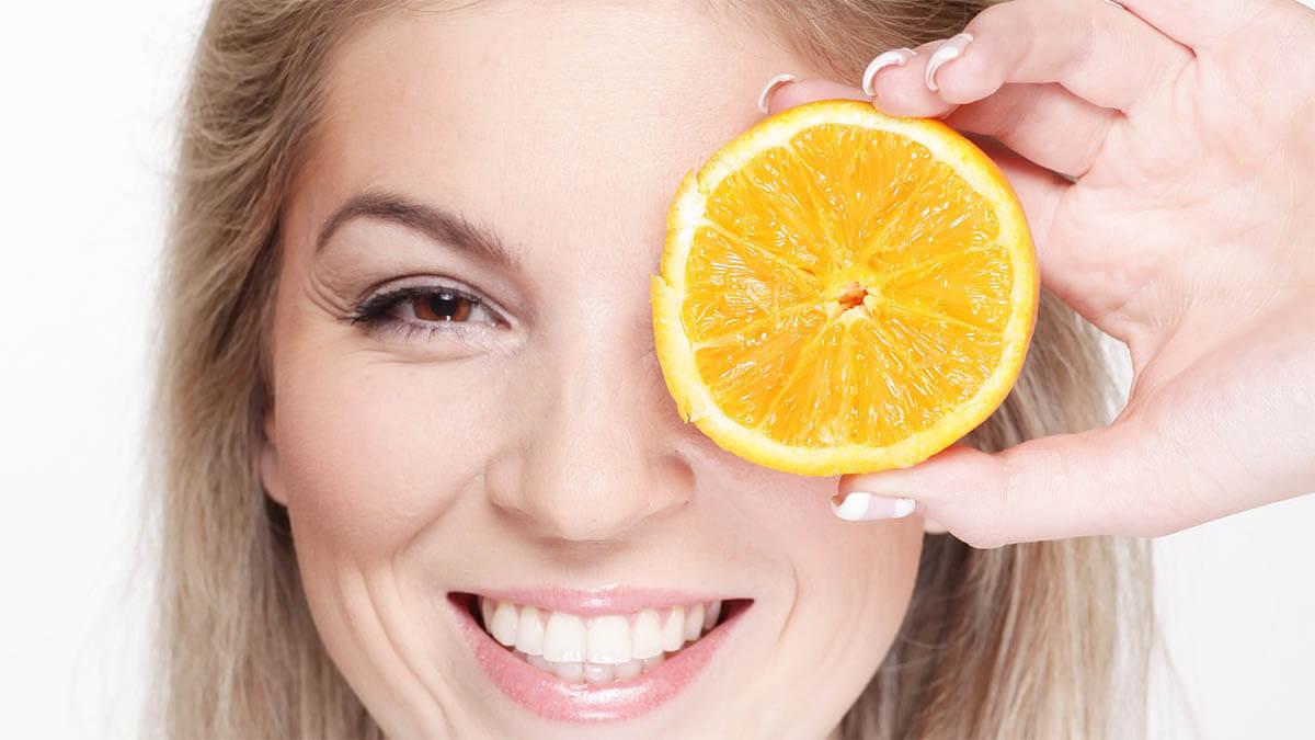 frau-haelt-sich-orange-vor-auge