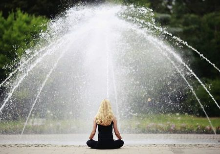 frau meditieren springbrunnen