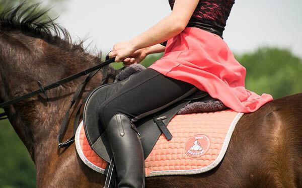 frau reitet auf pferd abgeschnitten bauch