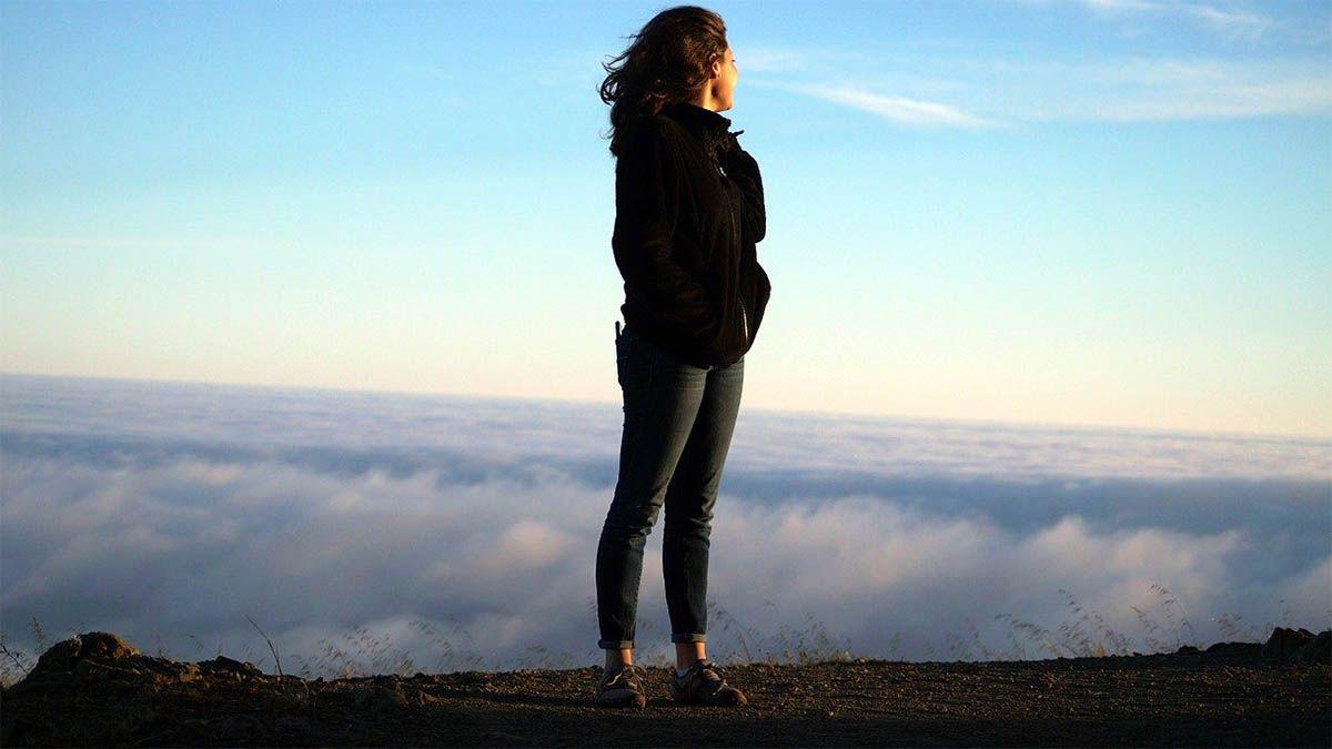 frau selbstbewusst blick ueber wolken