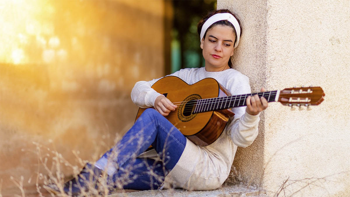frau-spielt-gitarre-sonnenstrahlen
