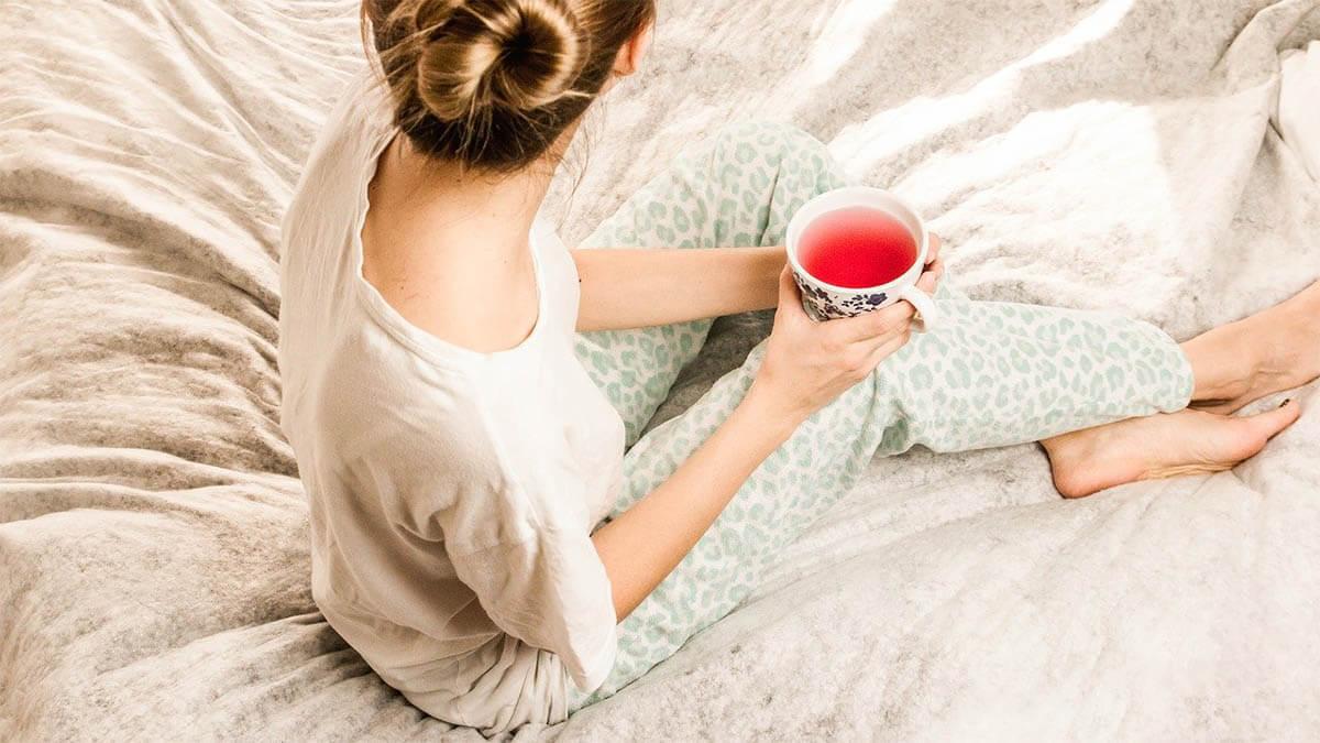 frau trinkt im bett einen tee