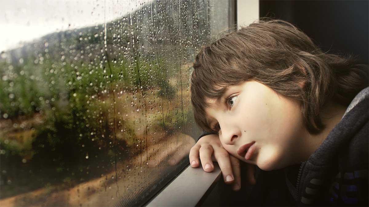 junge schaut traurig aus dem fenster