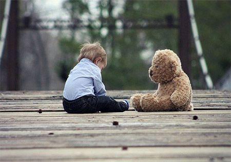 kind mit teddybaer auf terasse