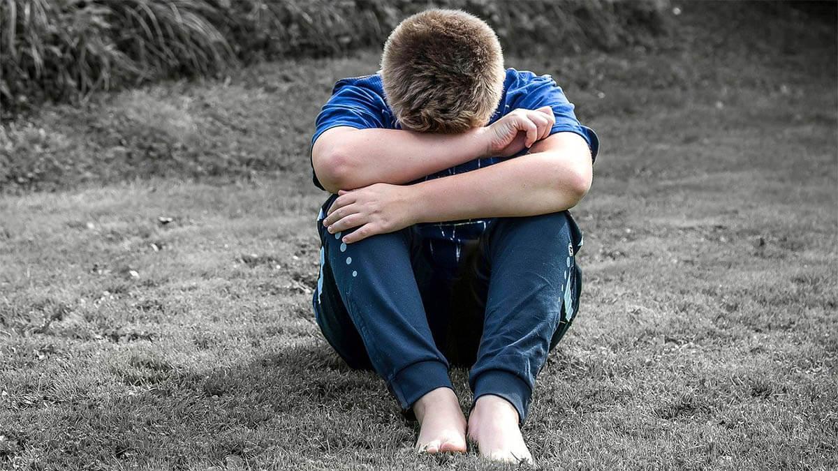 kind-sitzt-traurig-auf-dem-boden-haende-in-gesicht