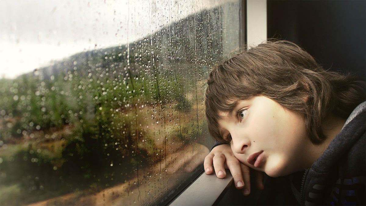 kind-traurig-regen-fensterscheibe