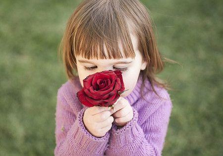 maedchen riecht an einer rose