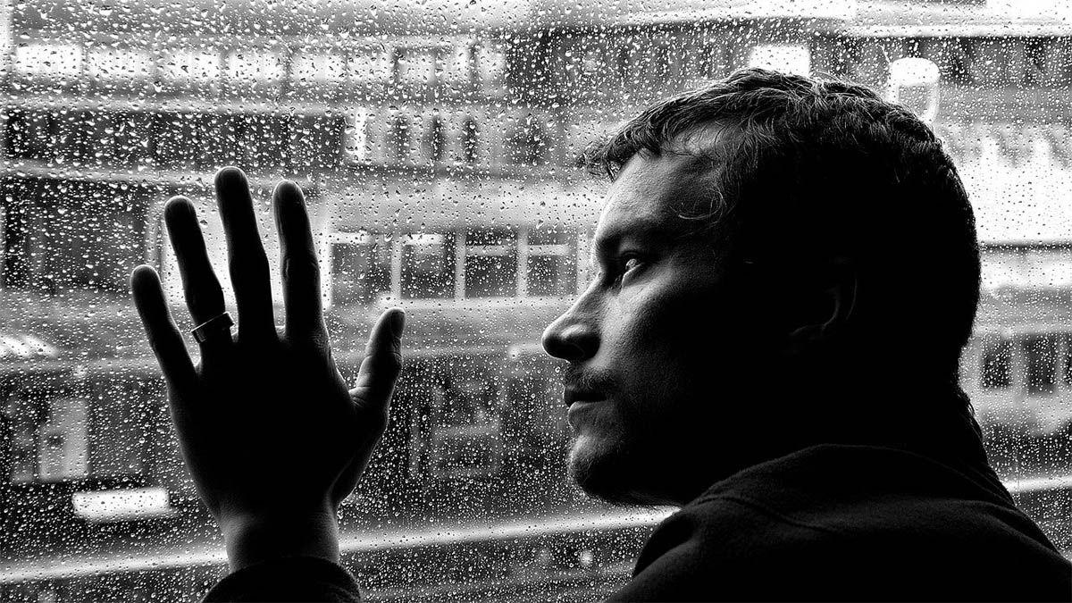 mann einsam schaut durch fensterscheibe