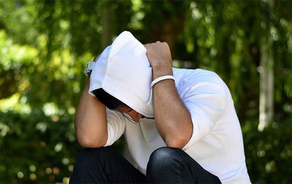 mann traurig kaputzenpulli gruen weiss