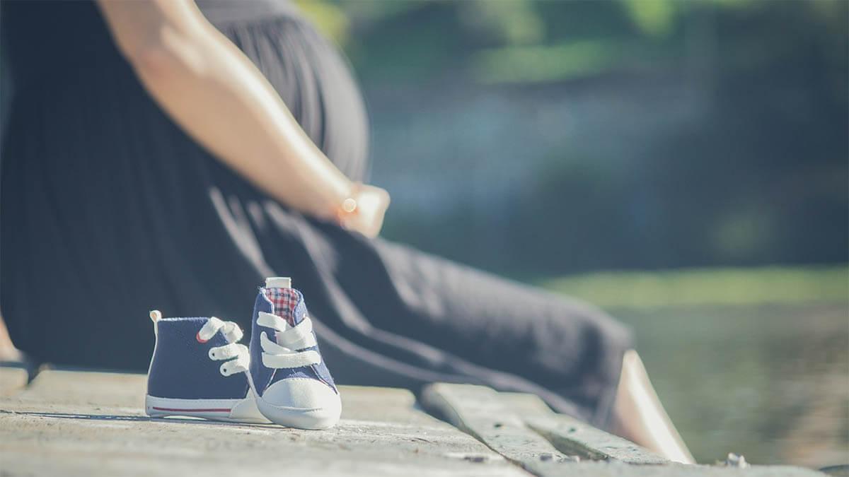 schwangere-sitzt-auf-steeg-babyschuhe