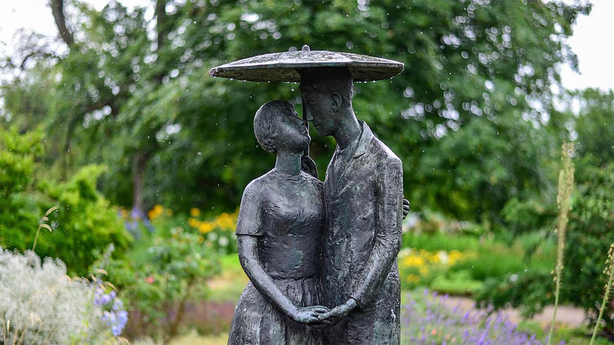 statue-mann-frau-verliebt-garten-regenschirm