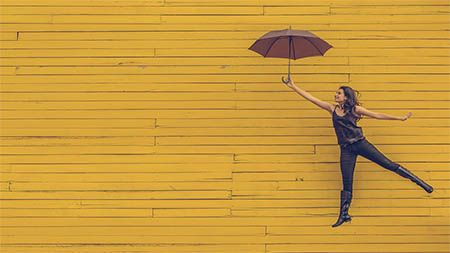 frau-gelbe-wand-regenschirm
