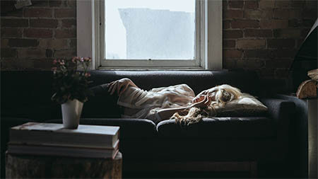 frau-liegt-muede-auf-sofa