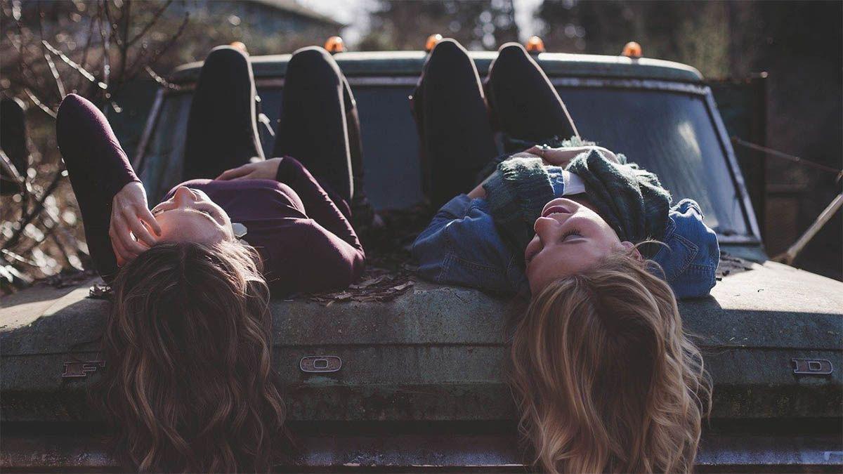 freundinnen-liegen-auf-motorhaube-und-lachen