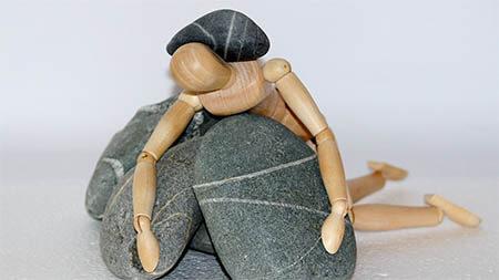 holzfigur-mit-steinen-beladen