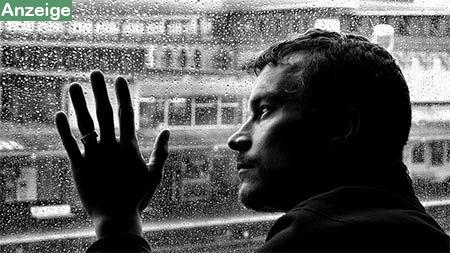 mann-einsam-verregnete-fensterscheibe