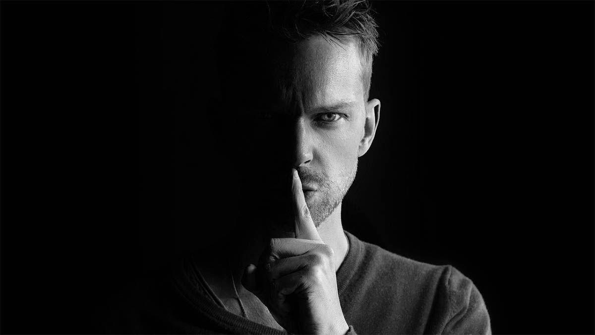 mann-finger-vor-mund-schweigen