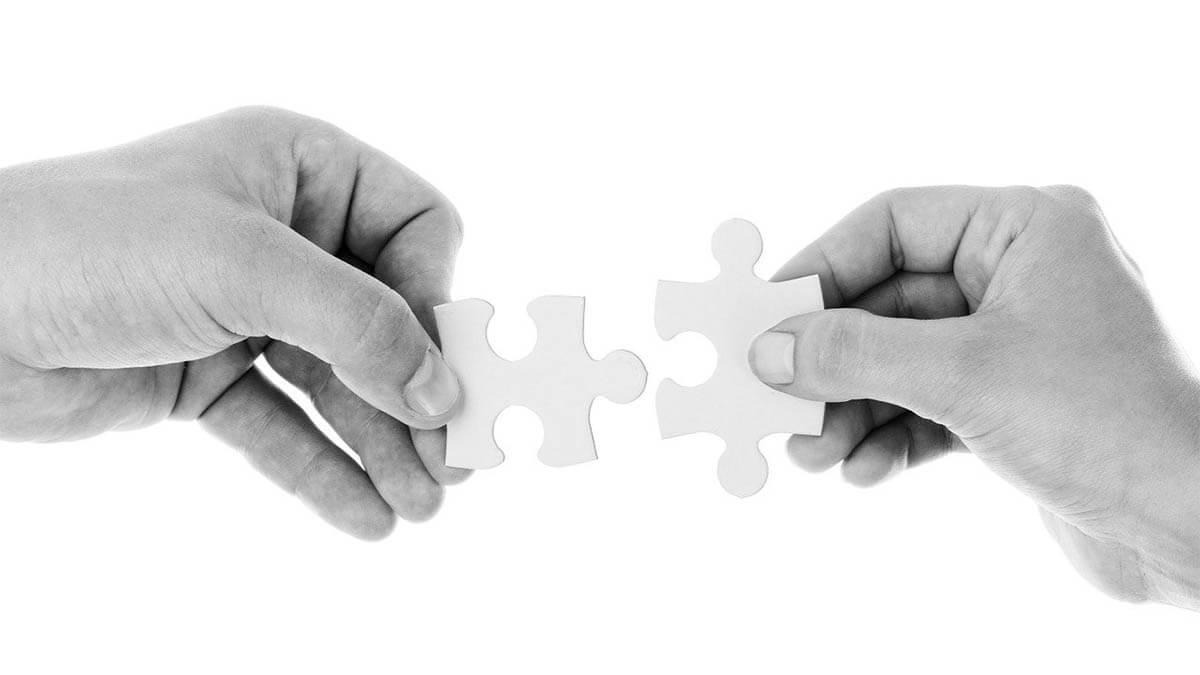 zwei-menschen-haende-stecken-puzzleteil-zusammen